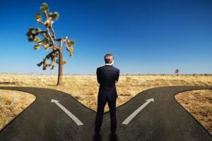 Geschftsmann muss sich bei einer Weg-Gabelung entscheiden